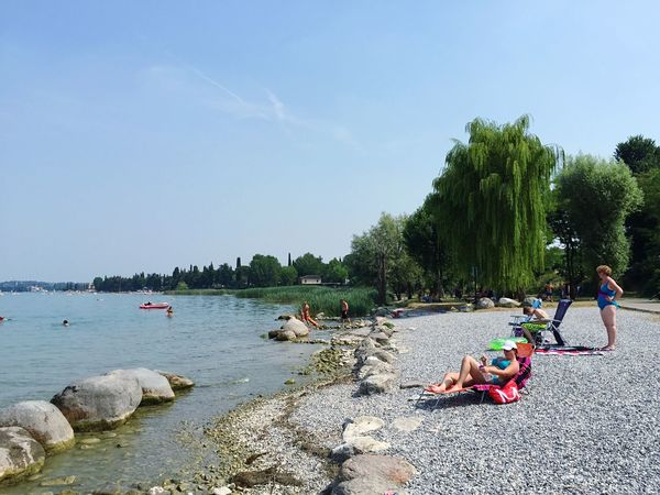 Del Garda Italian Lake Tree Real People Lifestyles Sky Sea Water Beach Nature Beauty In Nature Women Relaxation Summer Leisure Activity Outdoors Day Men Large Group Of People Clear Sky Weekend Activities Vacations PeschieraDelGarda