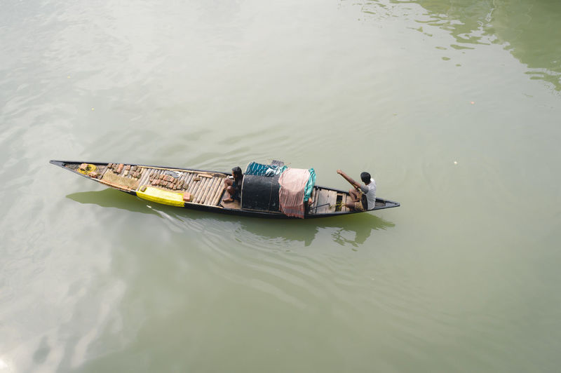 High angle view of men floating on lake