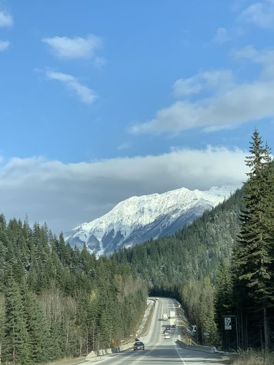 Cars on road amidst snowcapped mountains against sky