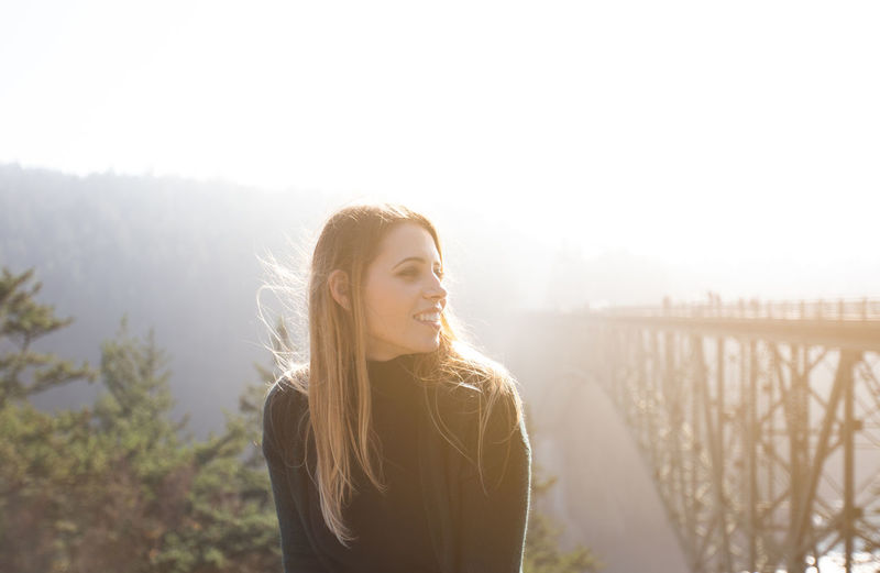 Smiling young woman looking away against bridge against clear sky