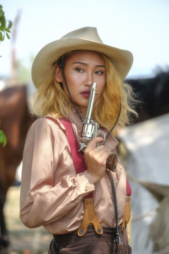 Woman wearing hat holding gun standing outdoors