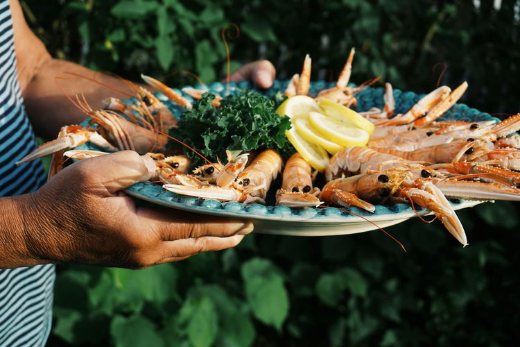 A man is serving crayfish at a garden party