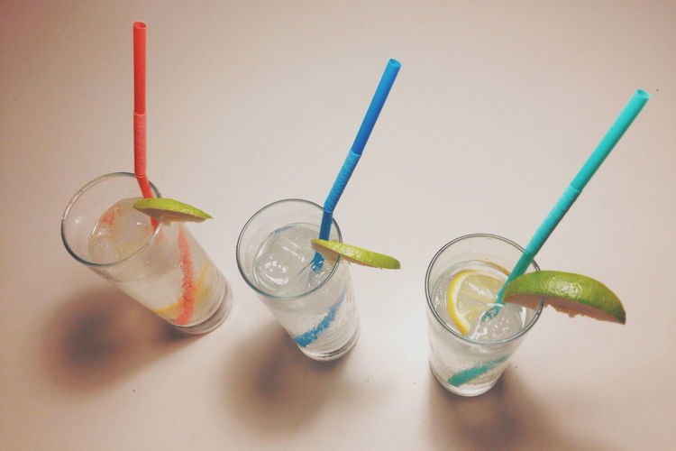 High angle view of highball cocktails with multi colored straws on table