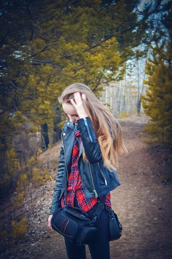 Young woman standing in forest with hand in hair during autumn
