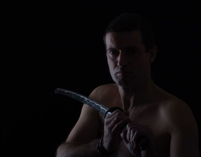 Portrait of mature shirtless man with sword against black background