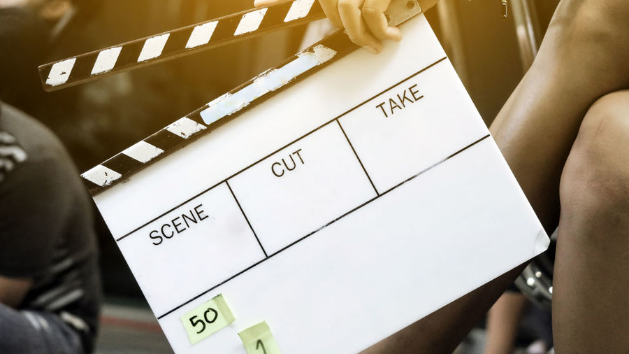 Cropped Image Of Woman Holding Movie Slate