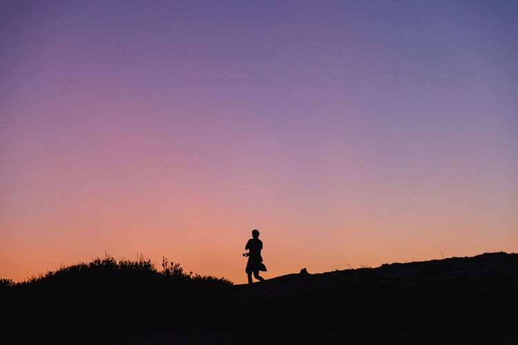 Silhouette of a woman standing against a clear sky during sunset