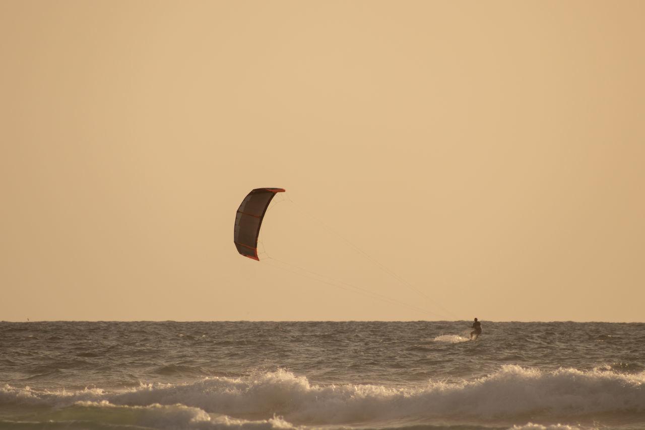 TWO PEOPLE IN SEA AGAINST SKY