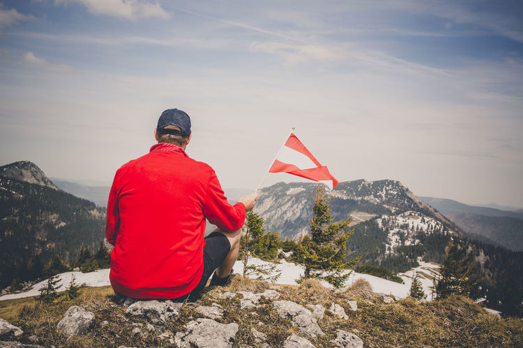 hiker with red sweater is holding an austria flag in the mountains Beauty In Nature Flag Leisure Activity Lifestyles Men Mountain Mountain Peak Mountain Range Nature One Person Patriotism Real People Rear View Red Scenics - Nature Sitting Sky Snowcapped Mountain Tranquility Winter