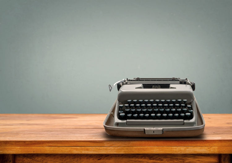 Old retro Typewriter on table with vintage gray gradient background 60s 70s 80s Antique Desk Machine Office Old-fashioned Retro Writer Antique Business Computer Keyboard Copy Space Indoors  No People Old-fashioned Retro Styled Studio Shot Table Technology Typewriter Wood - Material