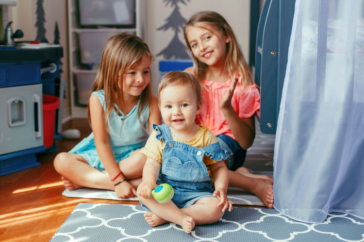 Portrait of smiling girls sitting on floor at home