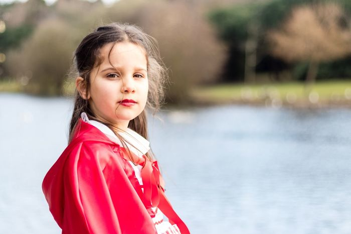 Little Red Riding Hood Childhood Girls One Person Real People Lake Portrait Focus On Foreground Elementary Age Leisure Activity Looking At Camera Outdoors Day Water Standing Nature