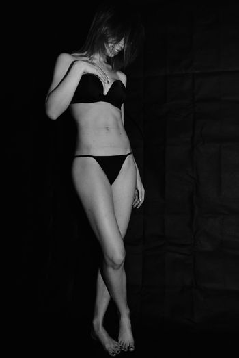 Full length of smiling sensuous woman standing against black background