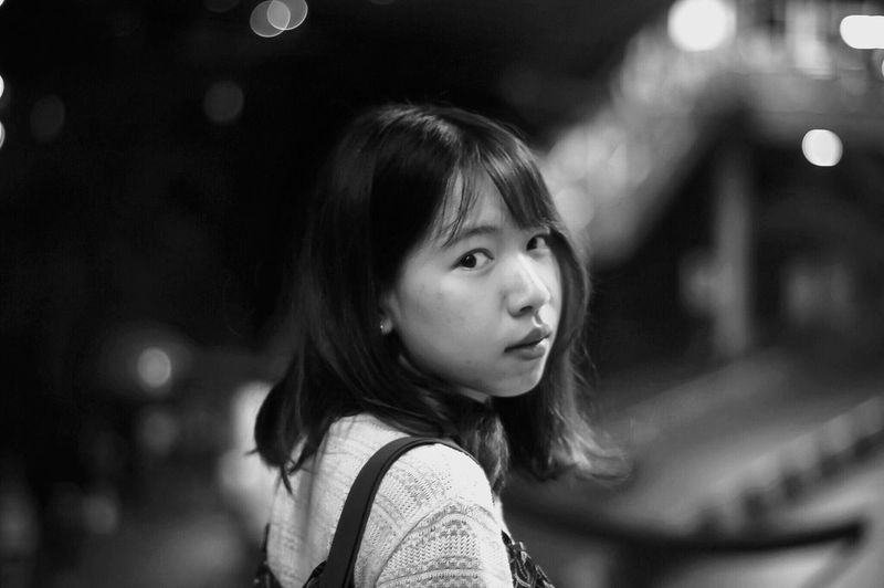 Close-Up Portrait Of Young Woman On Footpath At Night