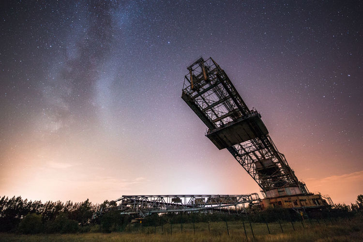 Low angle view of crane against sky at night