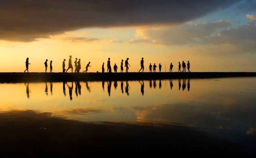 Silhouette people on lake against sky during sunset