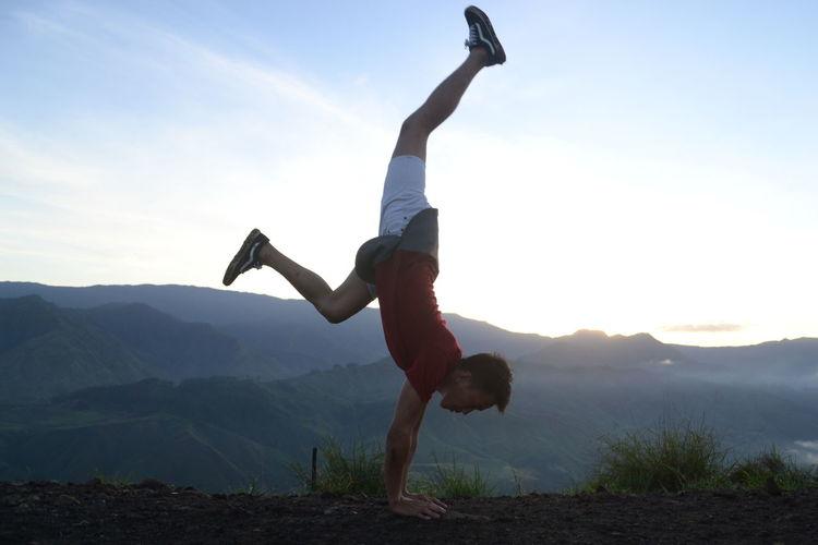 Full Length Of Man Doing Handstand On Mountain