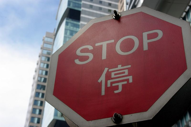 Low angle view of stop sign by buildings in city