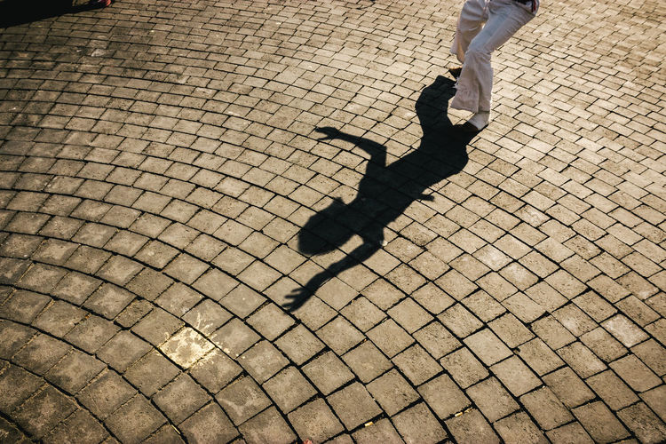 The shadow of a dancer projected on the floor. Adult Adults Only Culture Dancer Day Focus On Shadow Human Body Part Human Leg Low Section Men Motion One Man Only One Person Outdoors Pattern People Real People Shadow Silhouette Street Streetphotography Sunlight Sunset Tradition Travel