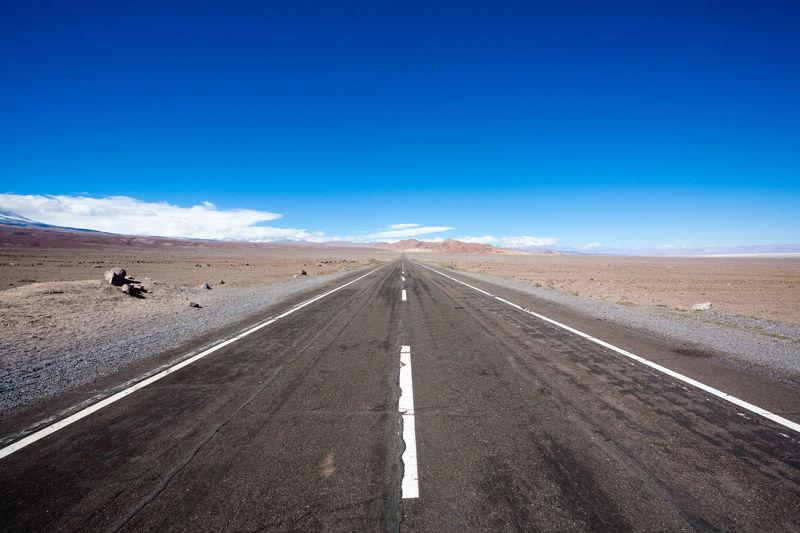 Road passing through desert against blue sky