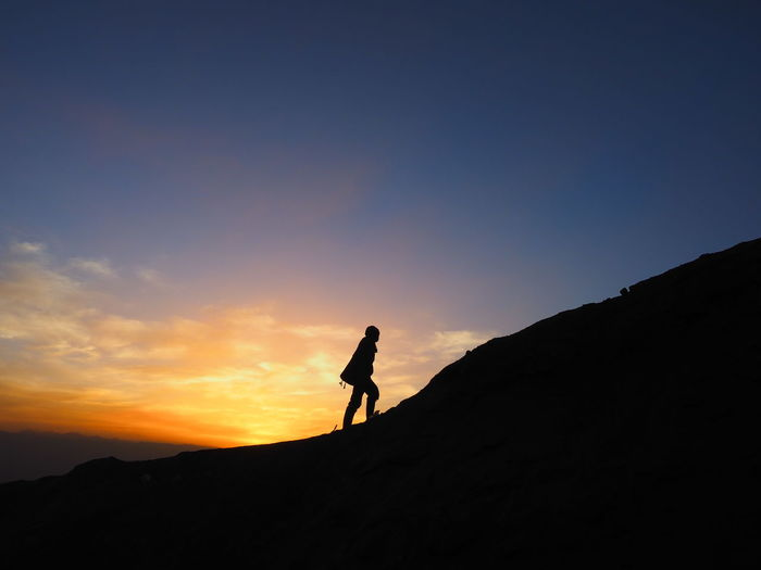 Silhouette person standing on mountain against sky during sunrise