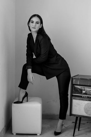Portrait of woman standing by vintage record player against wall