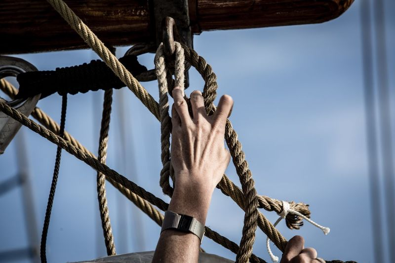 Low angle view of rope tied up on metallic structure