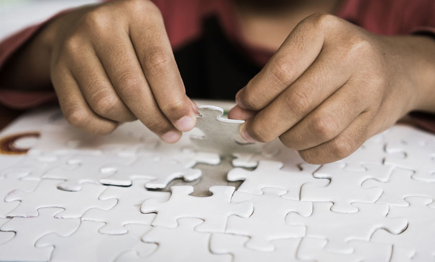 Cropped Hands Arranging Jigsaw Pieces