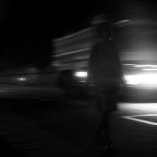 Rear view of person walking on illuminated street at night