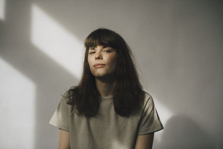 Portrait of young woman standing against wall at home