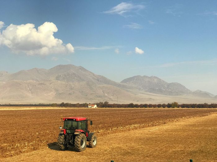 Land for sowing Sky Cloud - Sky Landscape Mountain Land Vehicle Agriculture Environment Land Rural Scene Field Transportation Nature Day Scenics - Nature Farm Mode Of Transportation Machinery Agricultural Equipment Beauty In Nature Agricultural Machinery