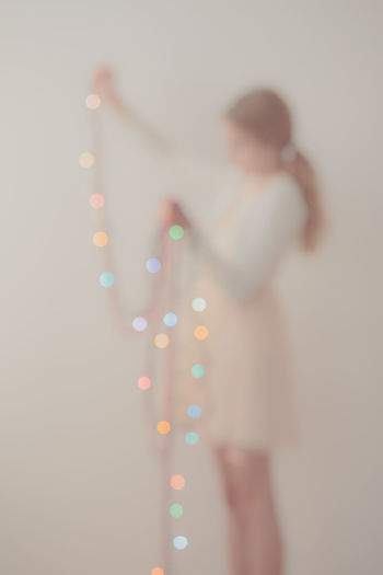 Out of focus portrait of young girl unwrapping colorful Christmas lights Anonymous Blonde Blur Blurred Celebration Christmas Christmastime Colorful Decorate Decorated Decoration Female Girl Holiday Home Lifestyles Light Ornament Out Of Focus Person Soft Tradition Unwrapping Vertical Young