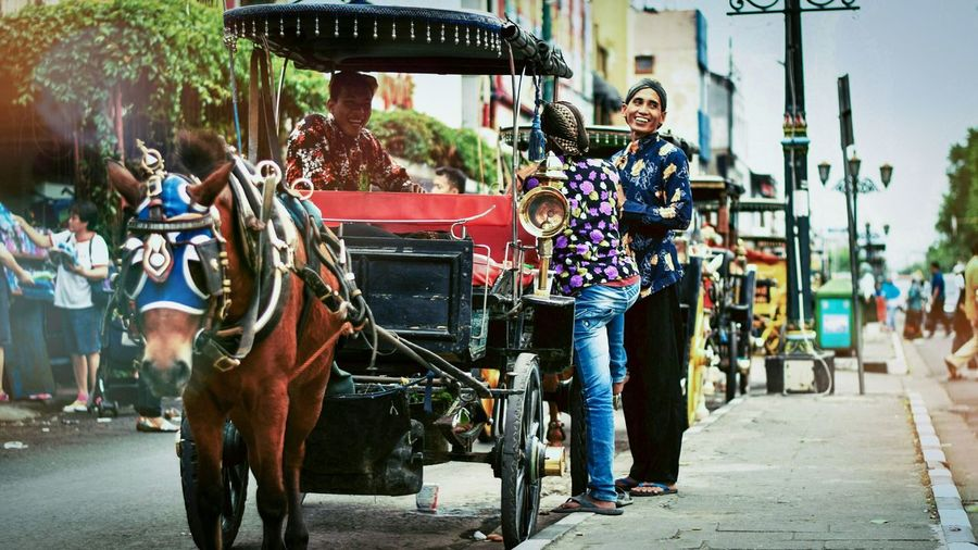 Happy friends with horse cart on road in city