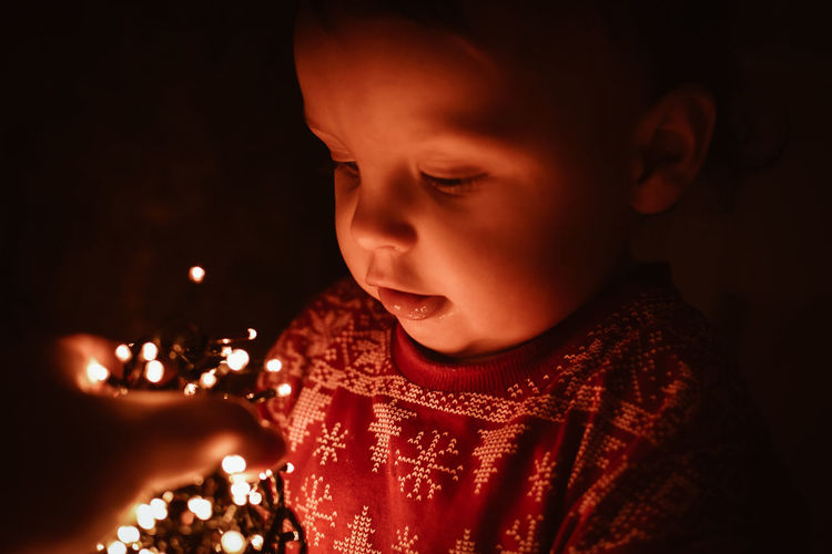 Close-up of cute girl looking at string lights in darkroom