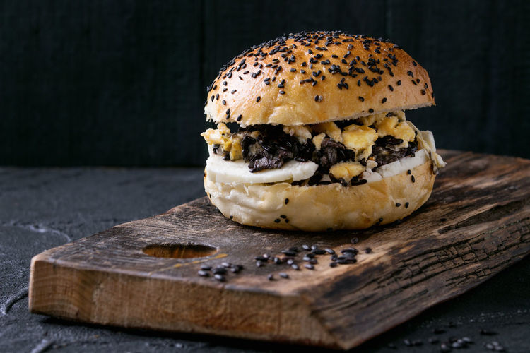 Homemade vegetarian burger with black rice, halloumi cheese and scrambled egg, served on wooden chopping board over black textured background. Rustic style Food Ready-to-eat Food And Drink Sandwich Fast Food Freshness Bun Bread Table Vegeterian Food Homemade Food Cutting Board Wood - Material Sesame Burger Black Beans Black Healthy Eating Scrambled Eggs Vegeterian Burger Vegetarian Food